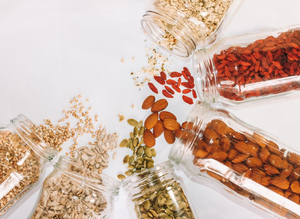 Seeds and goji berries spilling onto floor from glass jars